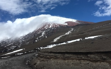 After a few kilometers downhill the clouds reveal the summit of Cotopaxi!